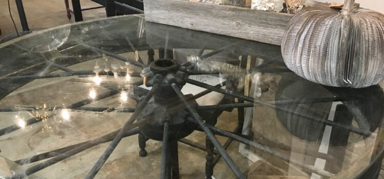 Table made from a wagon wheel with a glass top