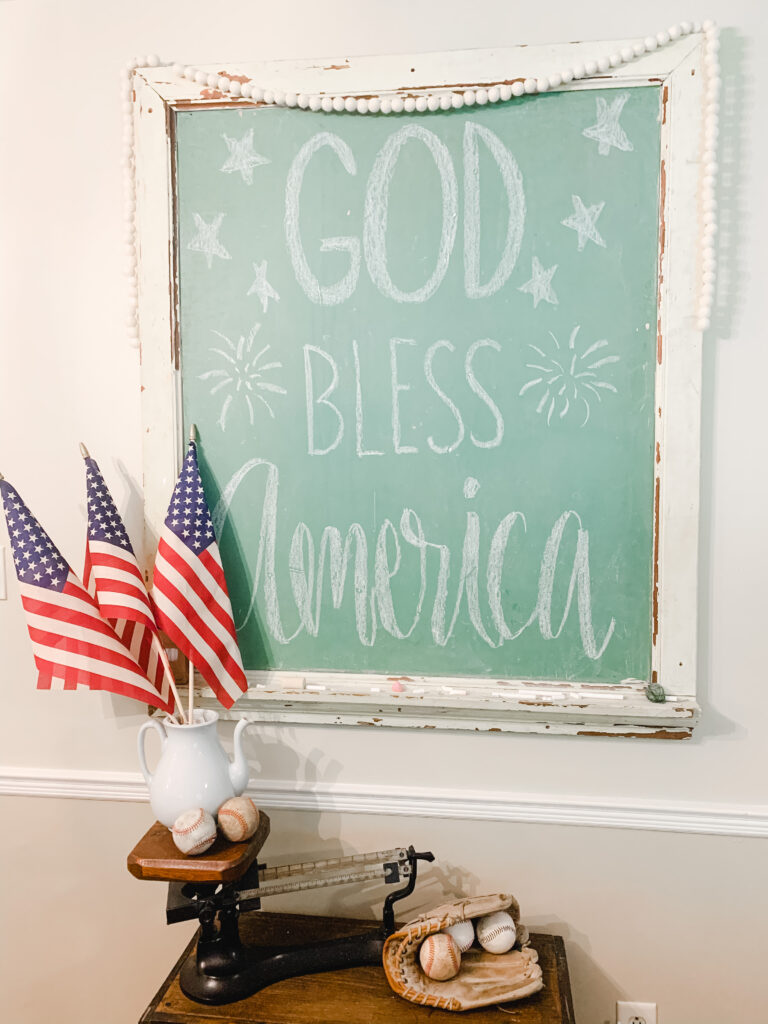 """American flags and baseballs displayed in front of a chalkboard with """"God Bless America."""""""
