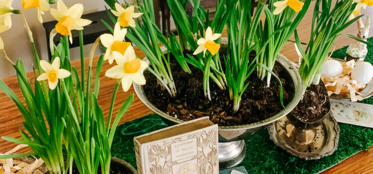 Dining room Easter tablescape with daffodils, vintage books and postcards