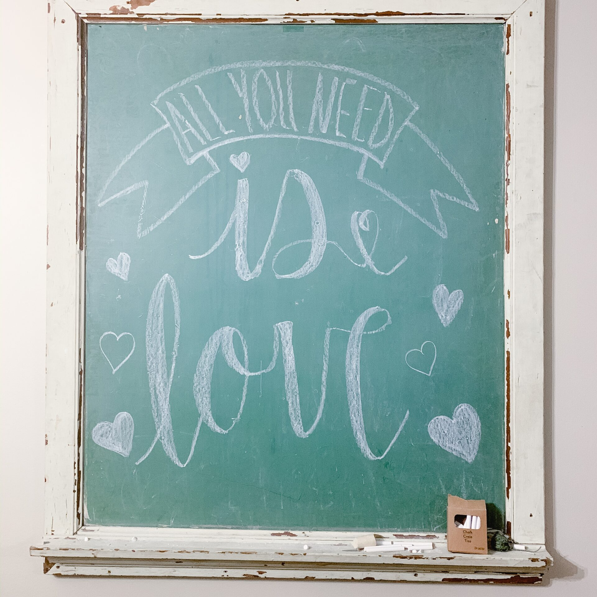 Antique chalkboard with All you need is love hand lettered