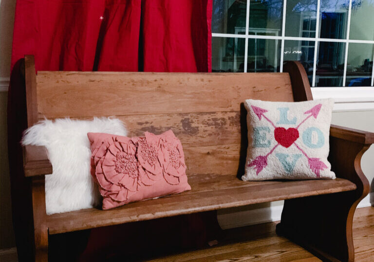 Church pew with pink pillow and red drapes for Valentine's Day