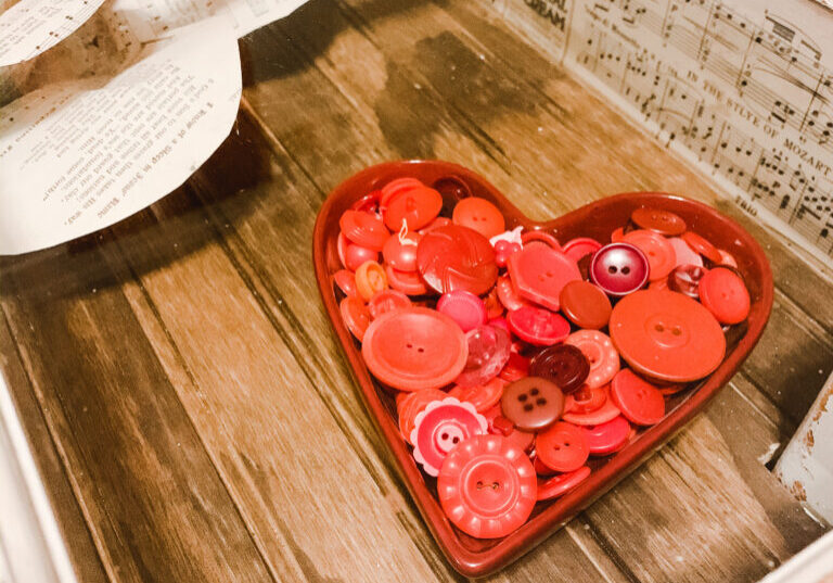 Heart shaped candy dish full of red vintage buttons for Valentine's Day decor